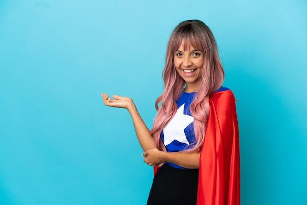 Молодая супергеройская женщина с розовыми волосами изолирована на синем фоне, протягивая руки в сторону, приглашая прийти