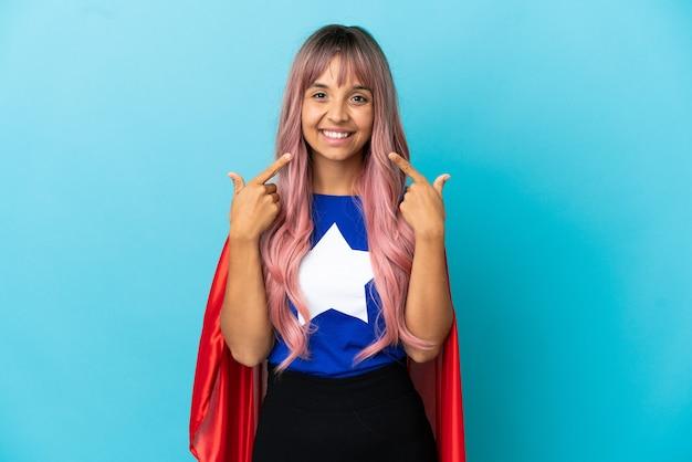 엄지손가락 제스처를 주는 파란색 배경에 고립 된 핑크 머리를 가진 젊은 슈퍼 히어로 여자