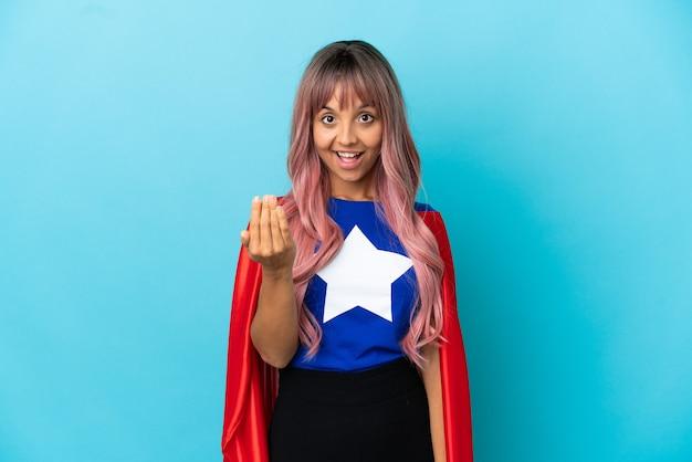 Молодая женщина супергероя с розовыми волосами, изолированные на синем фоне, приглашая прийти с рукой. счастлив что ты пришел