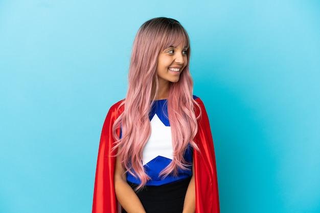 Молодая супергеройская женщина с розовыми волосами изолирована на синем фоне, смотрящая сторона