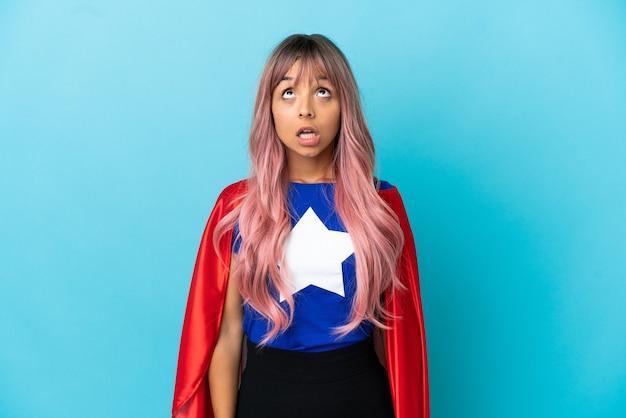 Молодая супергеройская женщина с розовыми волосами, изолированными на синем фоне, смотрит вверх и с удивленным выражением лица