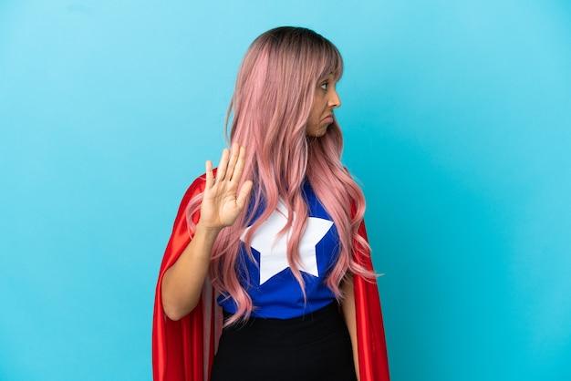 Молодая супергеройская женщина с розовыми волосами изолирована на синем фоне, делая жест стоп и разочарована