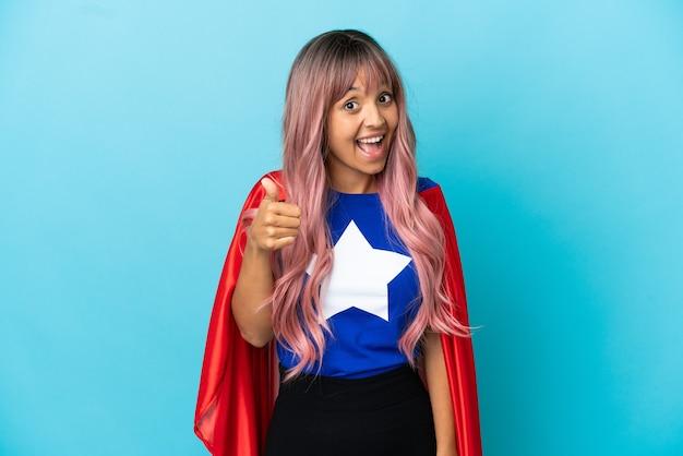 좋은 일이 일어났기 때문에 엄지손가락으로 파란색 배경에 고립 된 분홍색 머리를 가진 젊은 슈퍼 히어로 여성