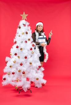 Young suprised beautiful woman with santa claus hat and standing behind the decorated christmas tree holding gifts and pointing above