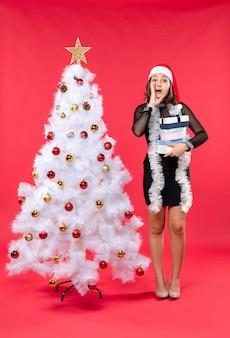 Giovane bella donna sorpresa con il cappello di babbo natale e in piedi vicino all'albero di natale decorato che tiene i regali e chiama qualcuno