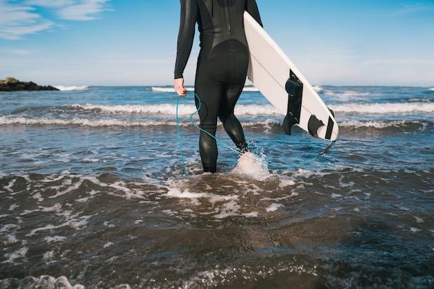 Молодой серфер входит в воду со своей доской для серфинга в черном костюме для серфинга. концепция спорта и водных видов спорта.