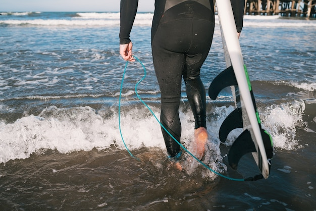 Young surfer entering into the water with his surfboard in a black surfing suit
