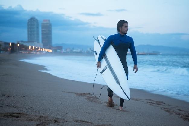 サーフボードを持って、サーフィンの準備ができて海岸に沿って歩いている若いサーファー