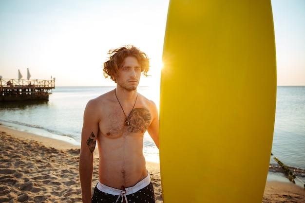 Молодой серфер держит доску для серфинга, стоя на пляже на закате