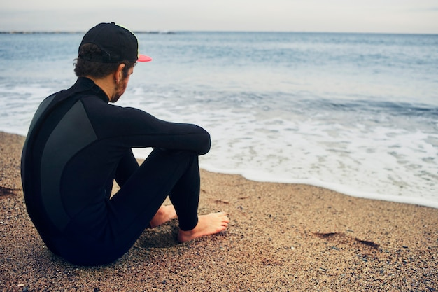 キャップを着てビーチで若いサーファー男