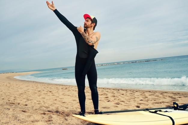 サーフボードとビーチで若いサーファー男