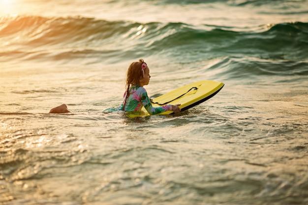 Молодой серфер катается на доске для серфинга с удовольствием на морских волнах