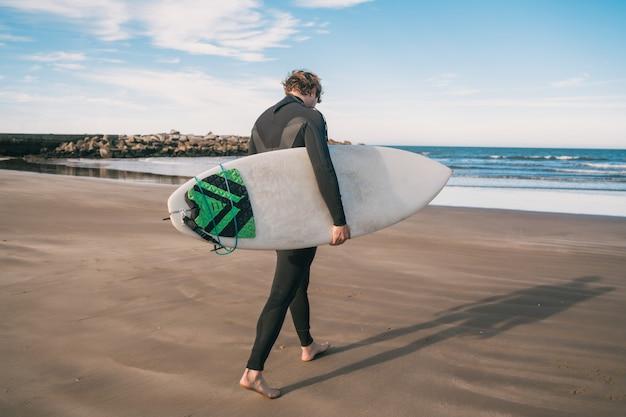 若いサーファーが黒いサーフィンスーツで彼のサーフボードを海に立っています。スポーツとウォータースポーツのコンセプトです。