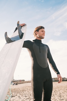 Молодой серфер стоит в океане со своей доской для серфинга в черном костюме для серфинга. концепция спорта и водных видов спорта.