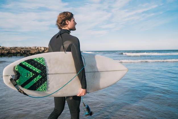Молодой серфер стоит в океане со своей доской для серфинга в черном костюме для серфинга
