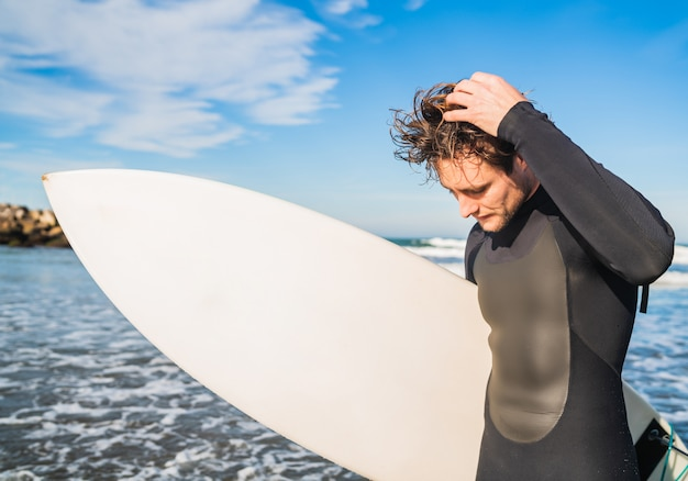 Young surfer standing in the ocean with his surfboard in a black surfing suit. sport and water sport concept.