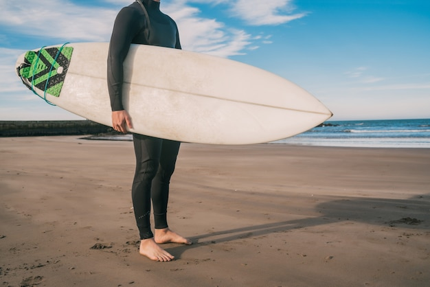 Young surfer standing in the ocean with his surfboard in a black surfing suit