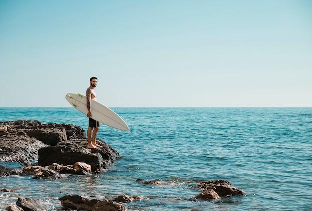 Молодой серфер стоит на скалистом берегу