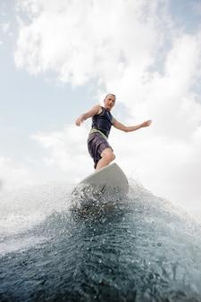 높은 블루 웨이브에 서있는 젊은 서퍼