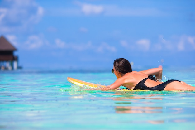 Young surfer woman surfing during beach vacation