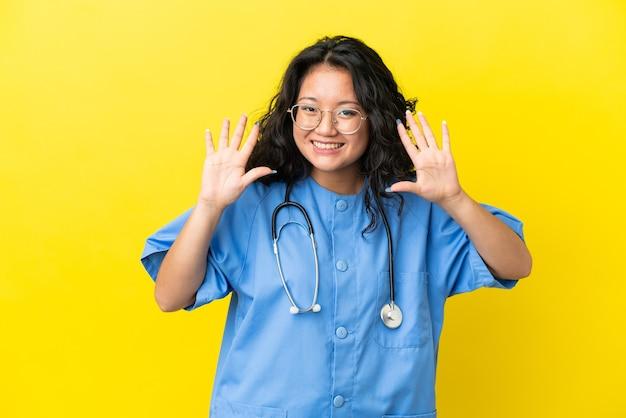 손가락으로 10을 세는 노란색 배경에 고립 된 젊은 외과 의사 아시아 여자