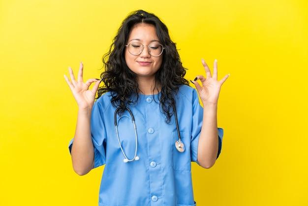 Молодой хирург-врач азиатская женщина изолирована на желтом фоне в позе дзен