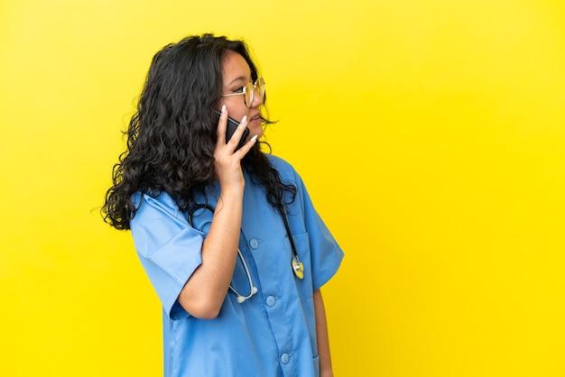 誰かと携帯電話との会話を維持黄色の背景に分離された若い外科医医師アジアの女性