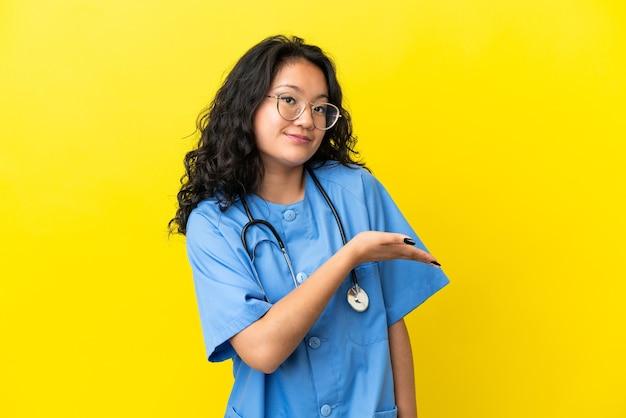 に向かって笑顔を見ながらアイデアを提示黄色の背景に分離された若い外科医医師アジアの女性