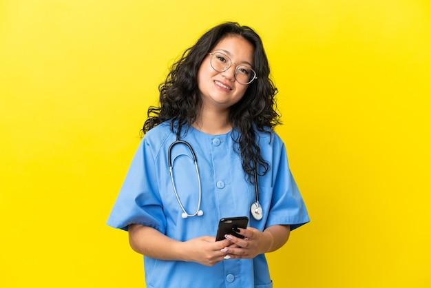 Молодой хирург-врач азиатская женщина изолирована на желтом фоне, отправляя сообщение с мобильного телефона