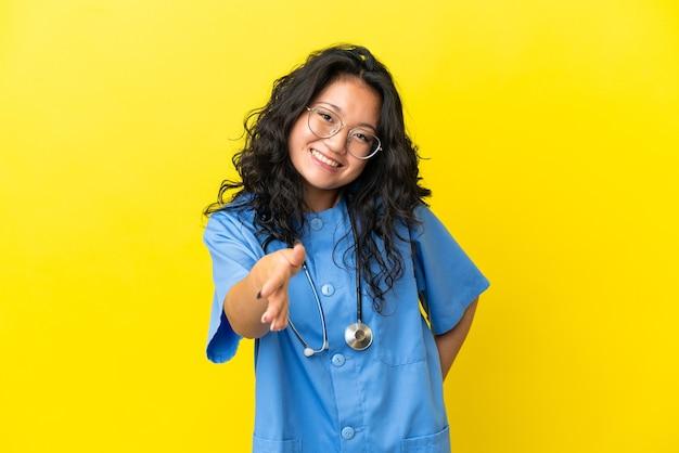 노란 배경에 격리된 젊은 외과 의사 아시아 여성이 좋은 거래를 성사시키기 위해 악수를 하고 있다