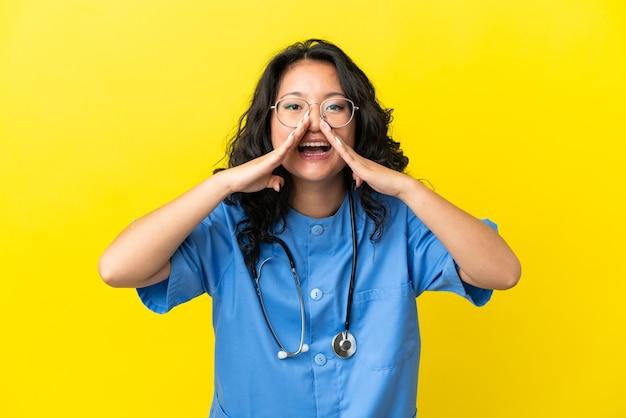 何かを叫び、発表する黄色の背景に分離された若い外科医医師アジアの女性