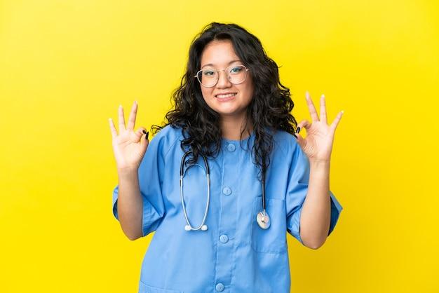 指でokサインを示す黄色の背景に分離された若い外科医医師アジア人女性