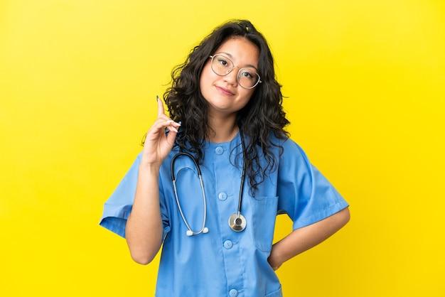노란색 배경에 격리된 젊은 외과 의사 아시아 여성이 최고라는 표시로 손가락을 들고 들어올립니다.