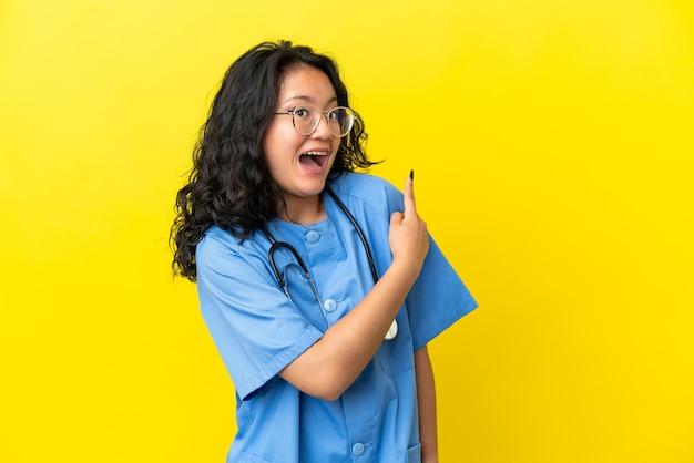 黄色の背景に分離された若い外科医医師アジアの女性は驚いて側を指しています