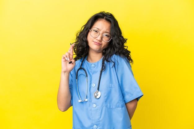 指が交差し、最高を願って黄色の背景に分離された若い外科医医師アジアの女性