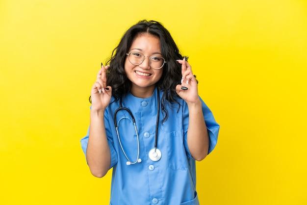 指を交差させて黄色の背景に分離された若い外科医医師アジア人女性