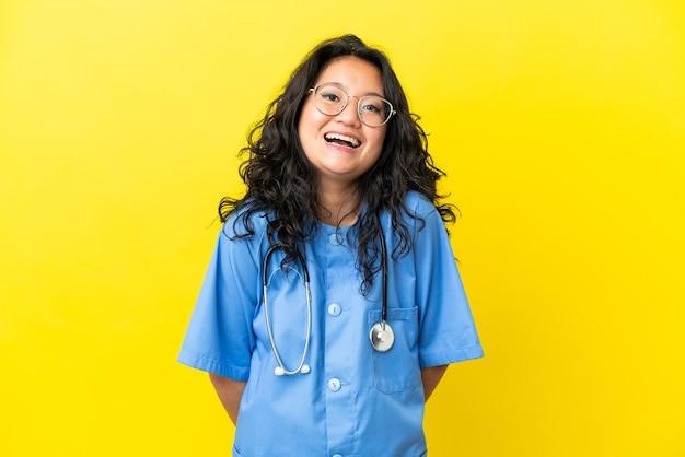 驚きの表情で黄色の背景に分離された若い外科医医師アジア人女性