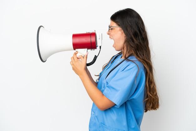 メガホンを介して叫んで白い背景で隔離の若い外科医医師白人女性