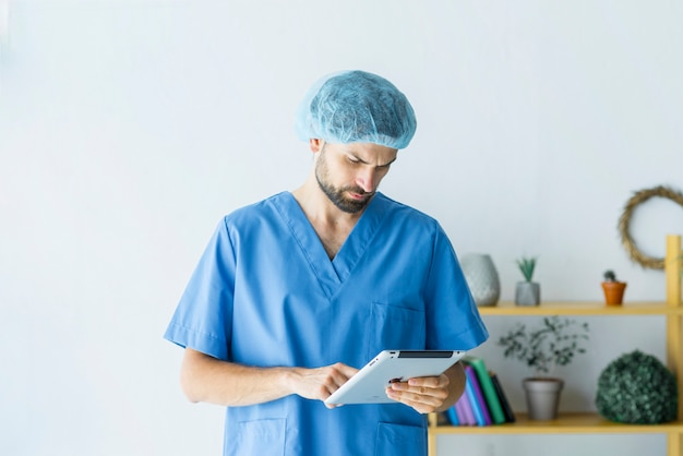 Young surgeon using tablet