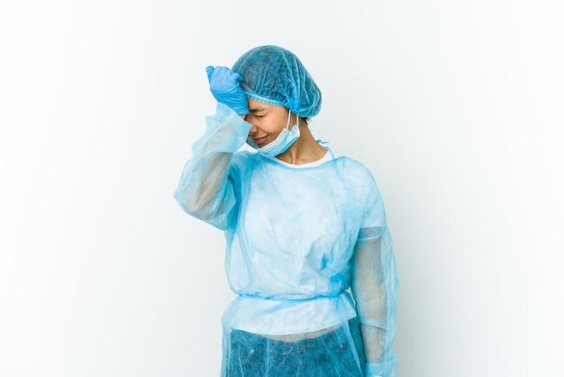 何かを忘れて、手のひらで額を叩き、目を閉じて白い壁に孤立した若い外科医の女性