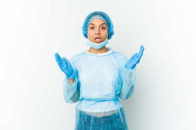 Young surgeon woman isolated on white wall surprised and shocked