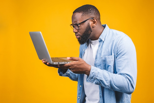 Young surprised african american man standing and using laptop computer