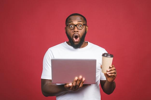 若者は立っていると赤い背景に分離されたラップトップコンピューターを使用してアフリカ人を驚かせた。コーヒーやお茶を飲みます。