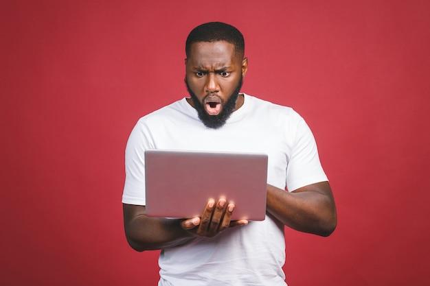 若者は立っていると赤い背景に分離されたラップトップコンピューターを使用してアフリカ人を驚かせた。