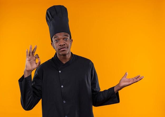 Giovane cuoco afroamericano sorpreso in uniforme del cuoco unico gesti il segno giusto della mano e indica il lato con la mano isolata sulla parete arancio