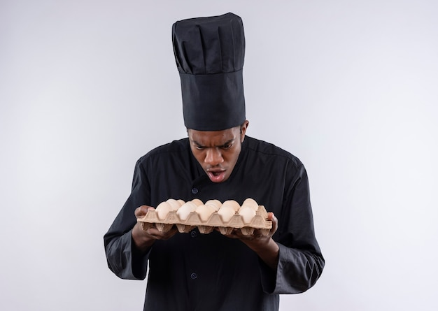 Young surprised afro-american cook in chef uniform holds batch of eggs isolated on white wall