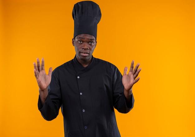 Il giovane cuoco afroamericano sorpreso in uniforme dello chef tiene le mani in alto guardando la telecamera sull'arancio con lo spazio della copia