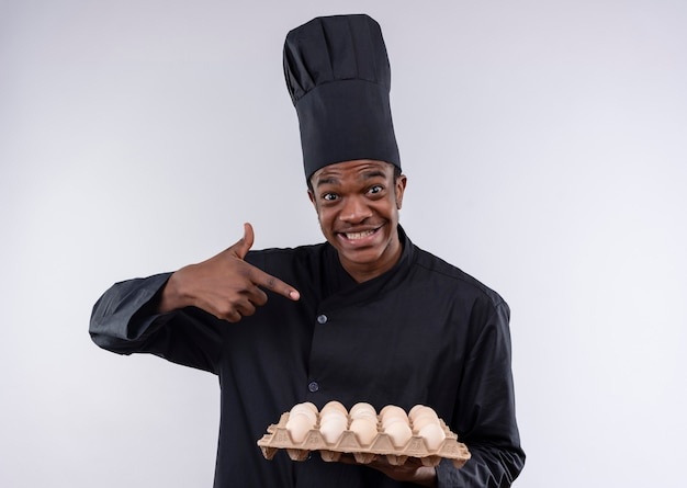 Young surprised afro-american cook in chef uniform holds and points at batch of eggs isolated on white wall