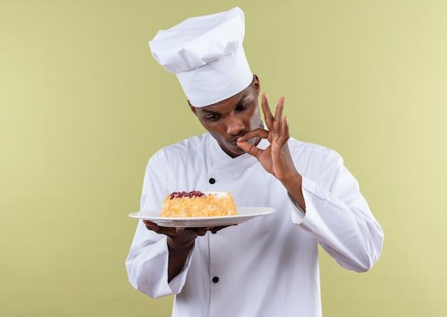 Il giovane cuoco afroamericano sorpreso in uniforme del cuoco unico esamina la torta sul piatto e sui gesti gustosi deliziosi con la mano isolata sulla parete verde