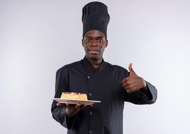 Молодой удивленный афро-американский повар в униформе шеф-повара держит торт на тарелке и показывает палец вверх на белом с копией пространства
